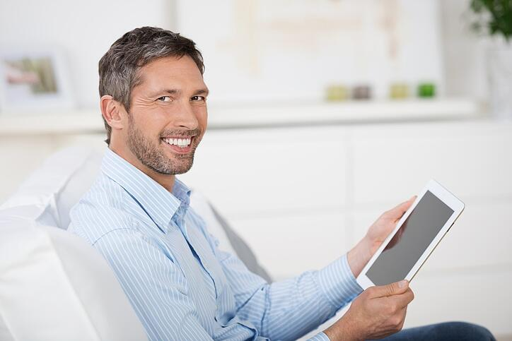 Side view of mature man reading ebook at digital tablet while sitting on sofa at home.jpeg